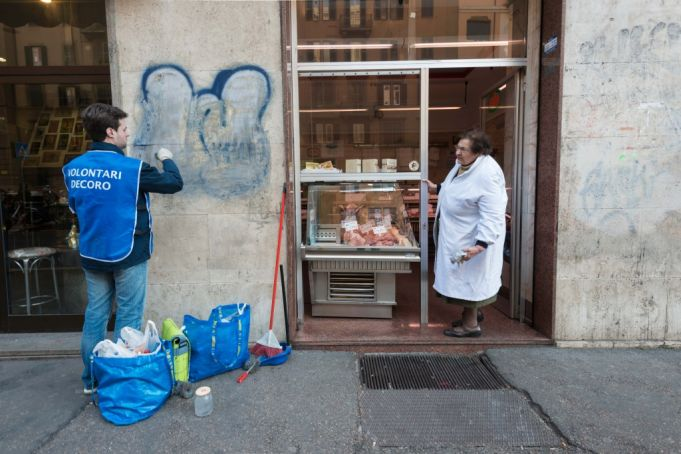 A Retake Roma volunteer removes graffiti from a shopfront on Viale Eritrea in the Nomentana district. Photo Matteo Natalucci.
