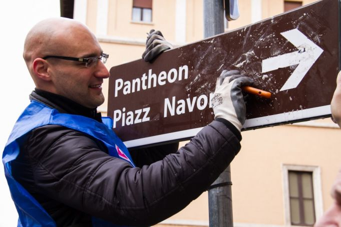 A Retake Roma volunteer removes stickers from a sign in Largo Argentina. Photo Virginia Vitalone.