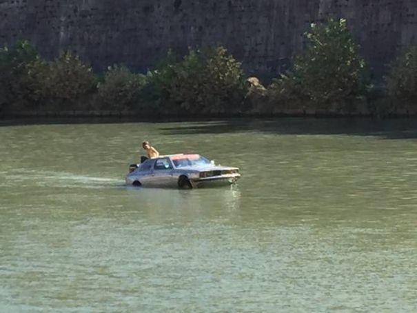 "Man ""sails"" vintage Maserati on Tiber in Rome"