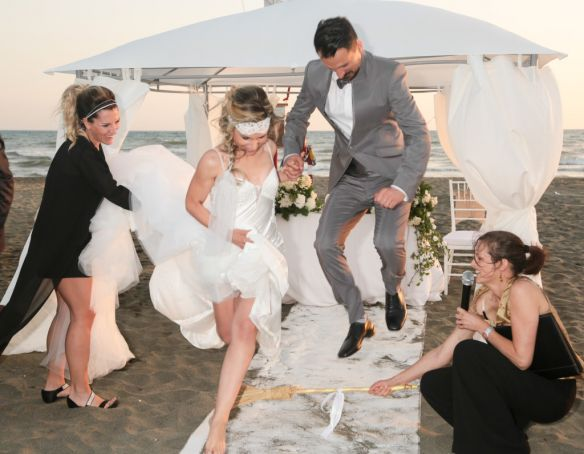 Alessia and Alessandro jumping the broom with celebrant Sarah Morgan (right) from Passaggi.